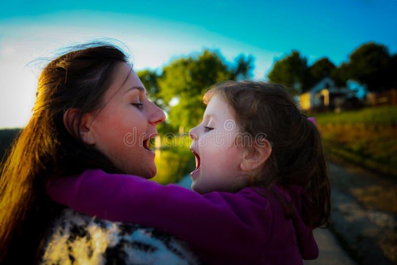 Giovane madre felice che abbraccia sua figlia dolce nei precedenti di bello prato del paese immagini stock libere da diritti