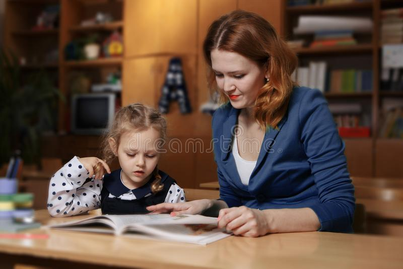 Giovane madre felice che aiuta sua figlia mentre studiando a casa fotografia stock libera da diritti