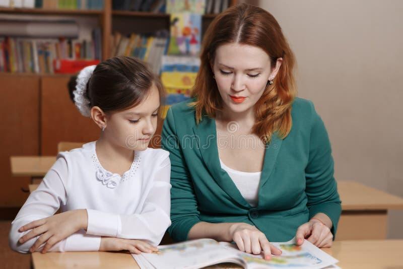 Giovane madre felice che aiuta sua figlia mentre studiando a casa fotografie stock libere da diritti