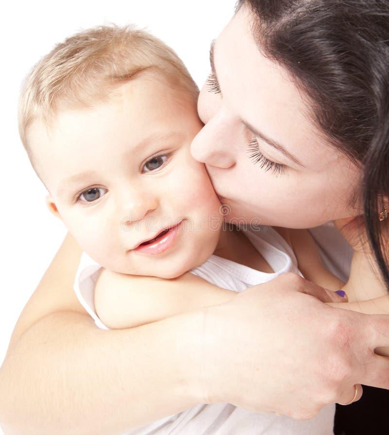 Giovane madre felice che bacia un bambino fotografia stock