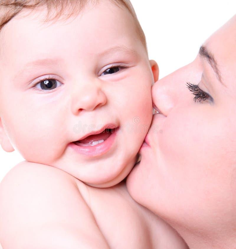Giovane madre felice che bacia un bambino immagine stock libera da diritti