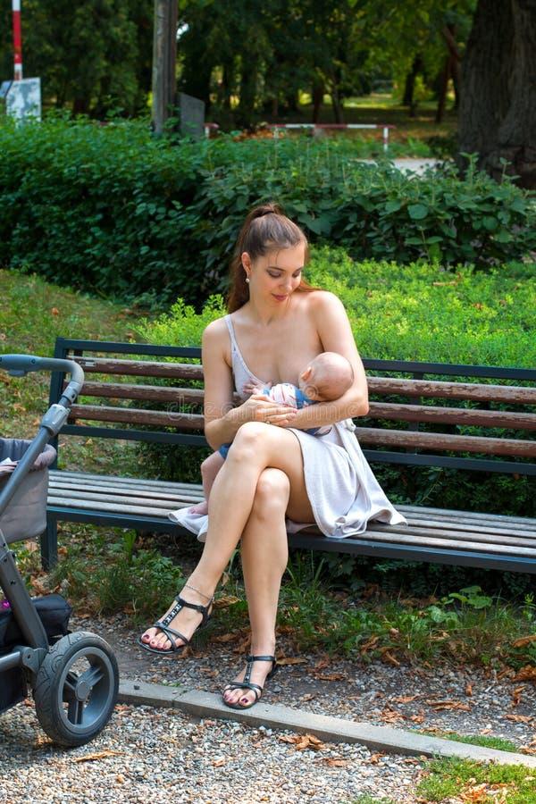 Giovane madre felice che si preoccupa il suo bambino nelle sue armi di amore e che allatta al seno in pubblico, sedentesi sul ban immagini stock