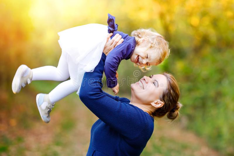 Giovane madre felice divertendosi la figlia sveglia del bambino, ritratto della famiglia insieme Donna con la bella neonata in na immagini stock