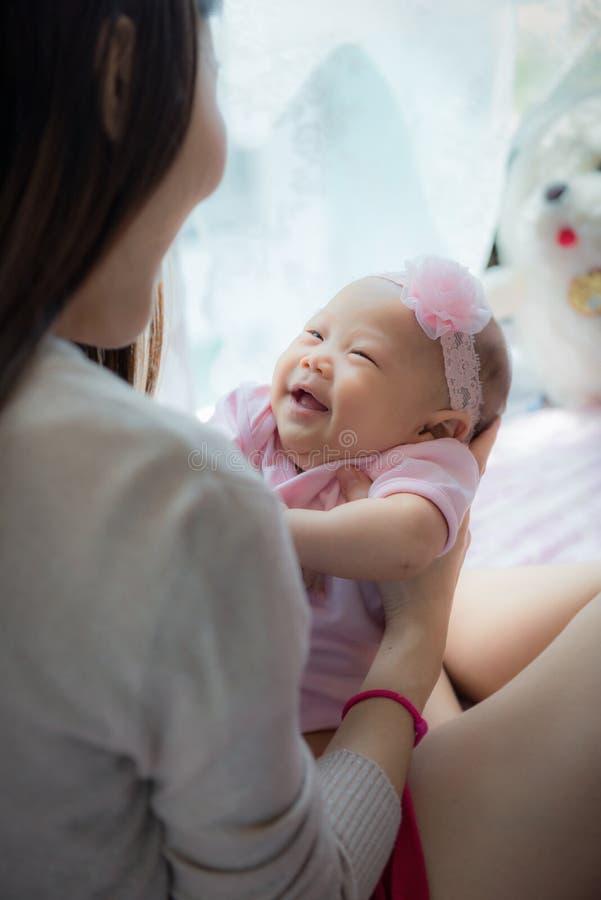 Giovane madre felice e la sua piccola figlia a casa, amando famiglia fotografia stock