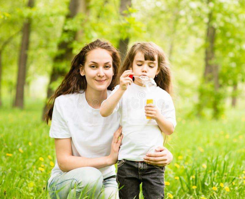 Giovane madre felice e le sue bolle di sapone di salto della figlia in parco fotografia stock