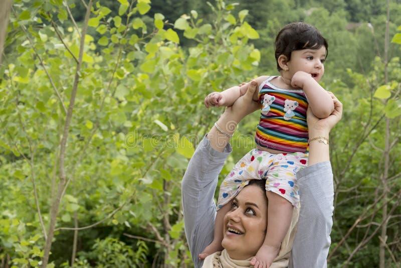 Giovane madre musulmana che tiene godere sopraelevato del piccolo bambino in o immagine stock libera da diritti