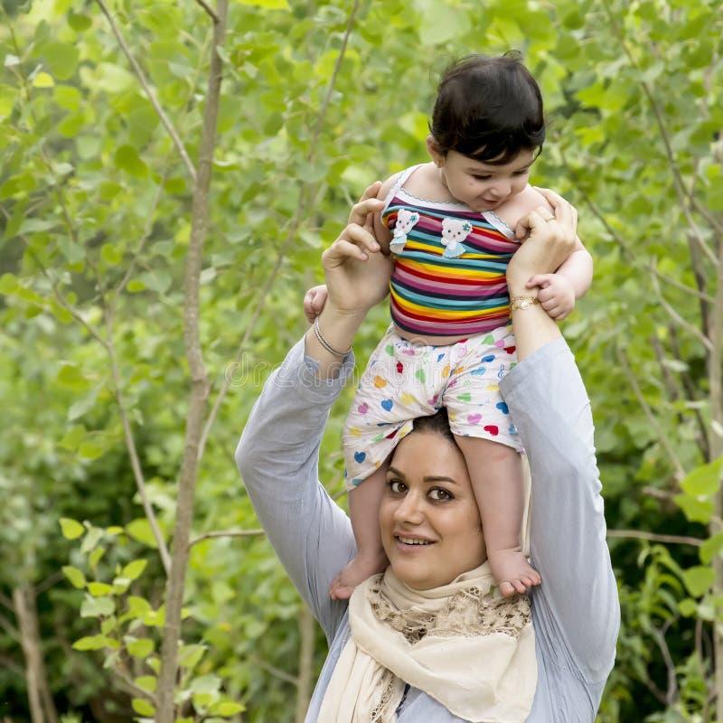Giovane madre musulmana che tiene godere sopraelevato del piccolo bambino in o immagini stock