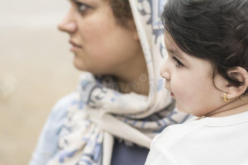 Giovane madre musulmana che tiene un piccolo bambino in all'aperto immagine stock libera da diritti