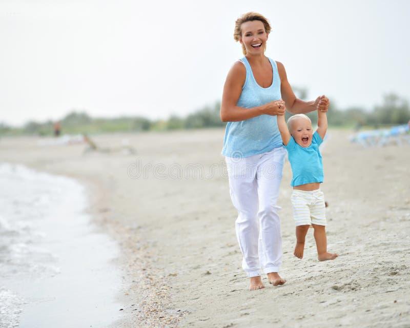 Giovane madre sorridente con funzionamento del piccolo bambino immagini stock libere da diritti
