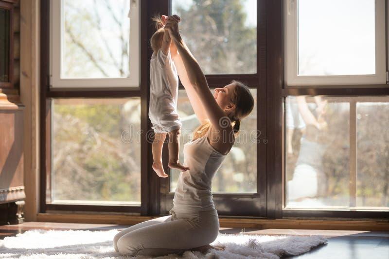 Giovane madre sportiva attraente che fa gli esercizi con il bambino a casa immagine stock libera da diritti