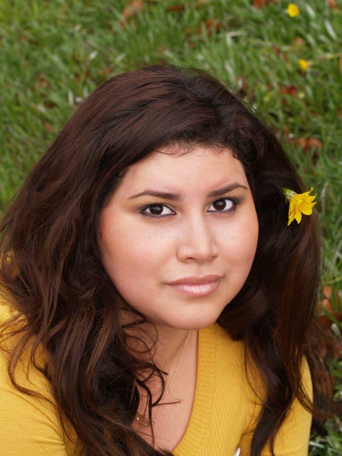 Giovane maglione grassoccio di colore giallo della donna con il fiore fotografia stock