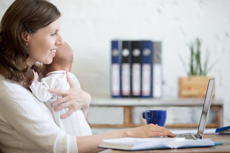 Giovane mamma che lavora con il suo bambino nell'ufficio fotografia stock