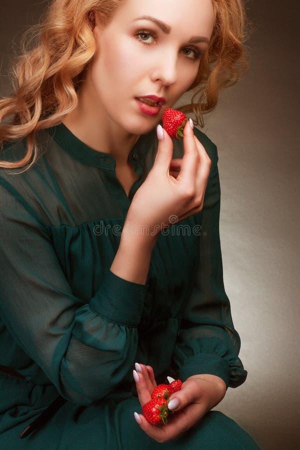 Giovane mangia fragole Ritratto in studio su sfondo multicolore fotografie stock