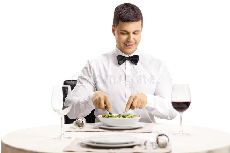 Giovane mangiatore di uomini elegante un'insalata ad un ristorante immagine stock libera da diritti
