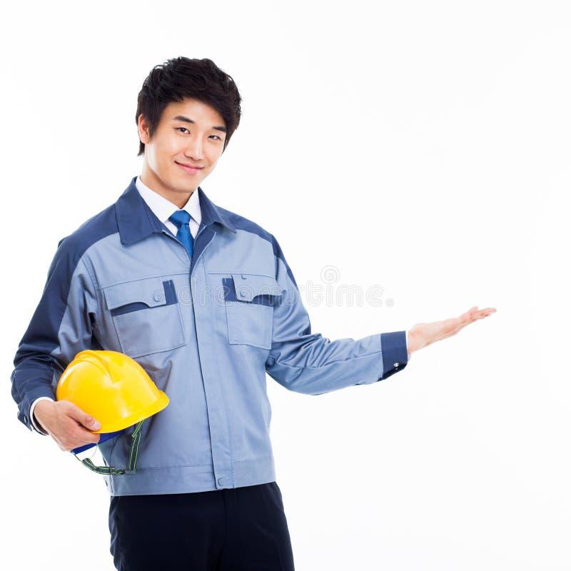 Giovane manifestazione asiatica dell'ingegnere qualcosa. fotografia stock libera da diritti