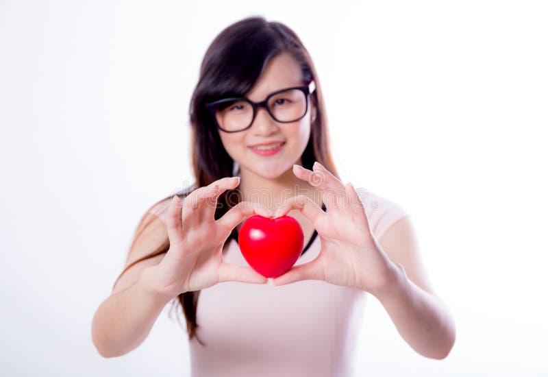 Giovane mano asiatica del cuore di manifestazione della donna fotografia stock