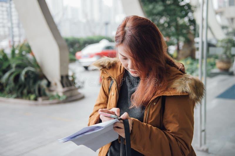 Giovane mano asiatica del viaggiatore della donna che indica lo schermo attivabile al tatto dello smartphone immagini stock libere da diritti