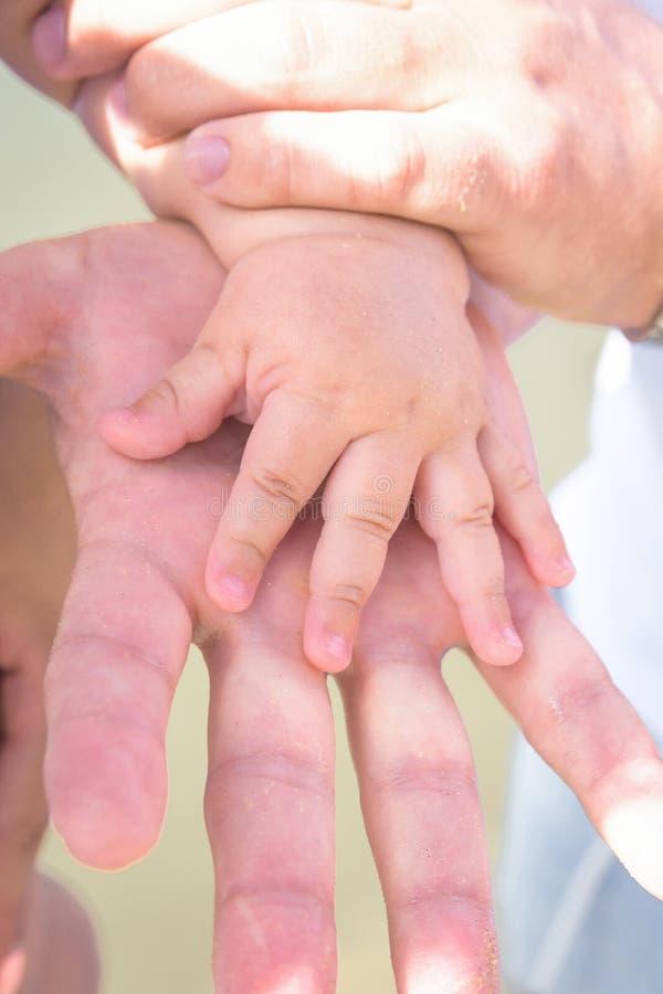 Giovane mano caucasica della tenuta dei genitori dell'uomo della donna di piccolo bambino del bambino Giorno di estate soleggiato immagini stock