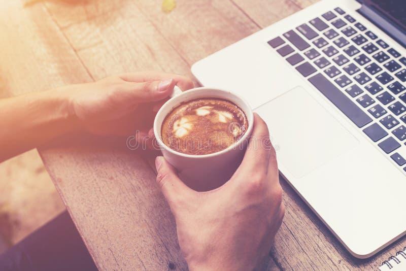 Giovane mano dell'uomo di affari che tiene il caffè della tazza e che per mezzo dei comp. del computer portatile fotografia stock