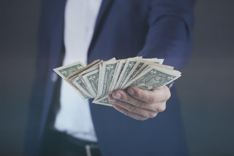 Giovane mano dell'uomo di affari che tiene soldi su fondo scuro fotografia stock libera da diritti