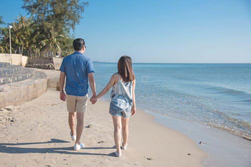 Giovane mano della tenuta delle coppie e camminare sulla spiaggia fotografia stock