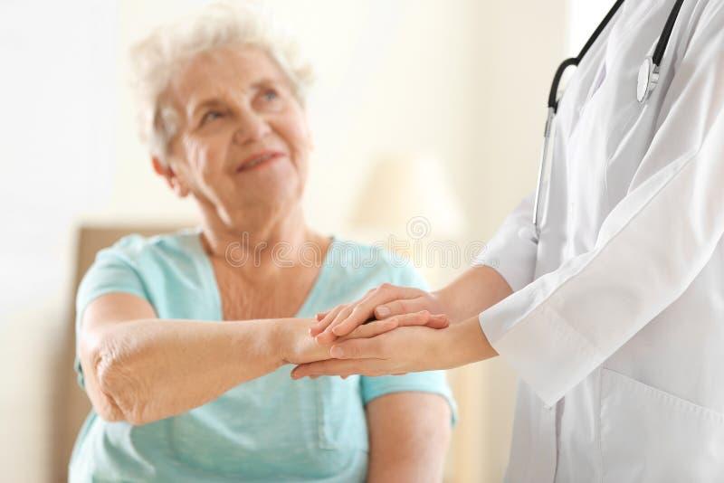 Giovane mano della tenuta di medico della donna anziana fotografie stock libere da diritti