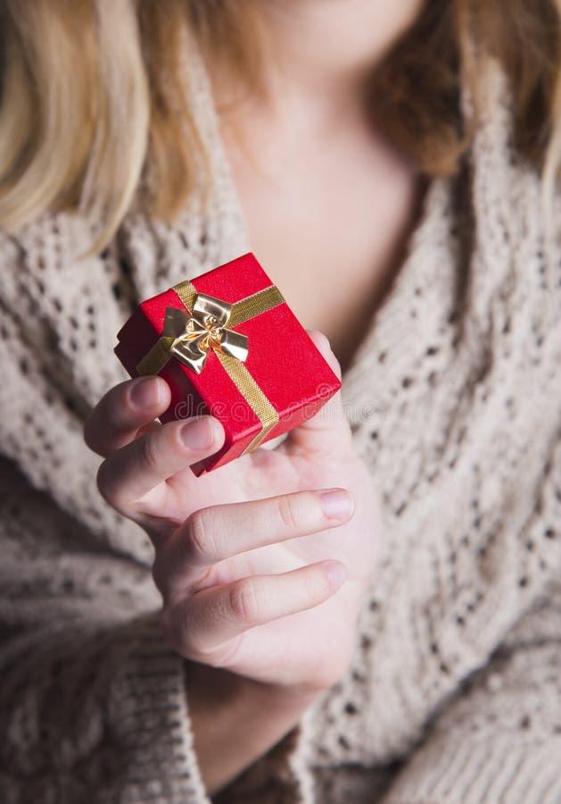 Giovane mano femminile che tiene il singolo contenitore di regalo rosso fotografia stock