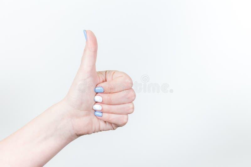Giovane mano femminile nel gesto di somiglianza con il pollice su isolato immagine stock