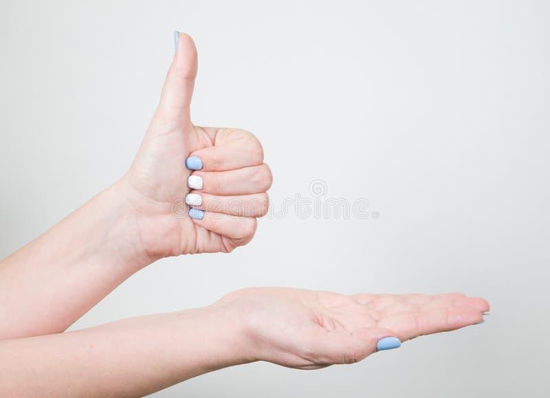 Giovane mano femminile nel gesto di somiglianza con il pollice su isolato fotografie stock