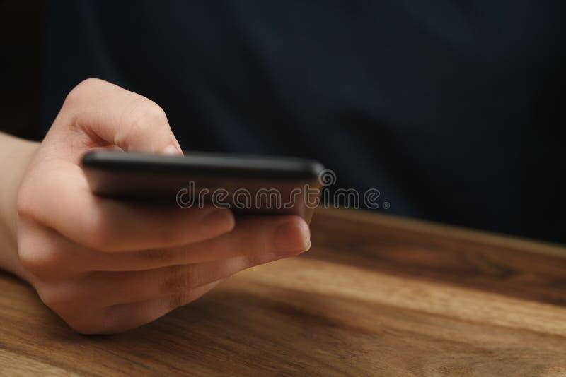 Giovane mano teenager femminile facendo uso dello smatphone che si siede al primo piano della tavola fotografia stock