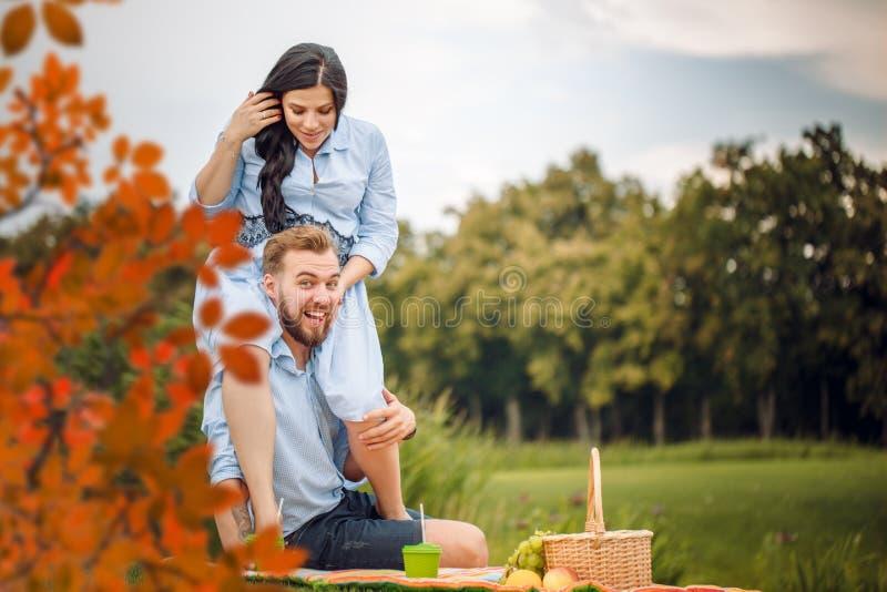 Giovane marito allegro felice della famiglia e la sua moglie incinta divertendosi insieme all'aperto, al picnic nel parco di esta fotografie stock libere da diritti