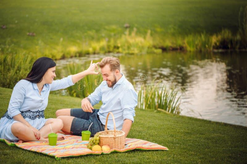 Giovane marito allegro felice della famiglia e la sua moglie incinta divertendosi insieme all'aperto, al picnic nel parco di esta fotografia stock libera da diritti