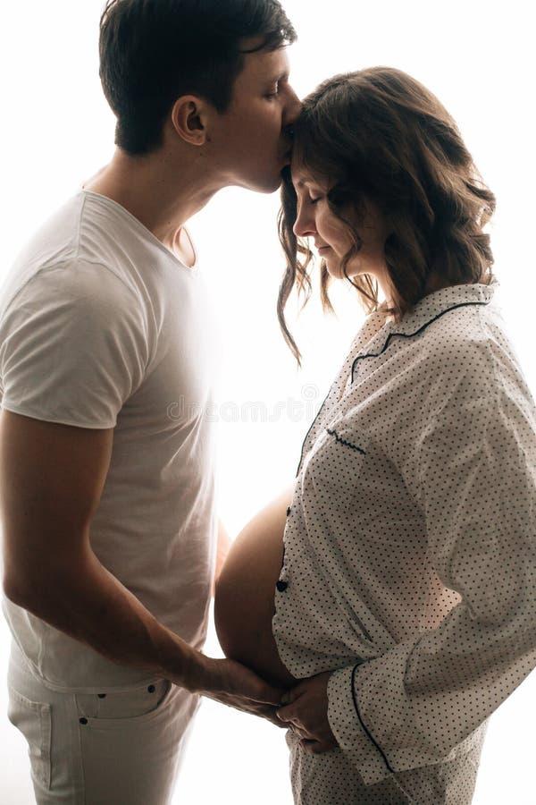 Giovane marito felice che bacia la sua moglie incinta e che tiene l'urto della pancia Famiglia, mamma e papà incinti alla moda in immagine stock