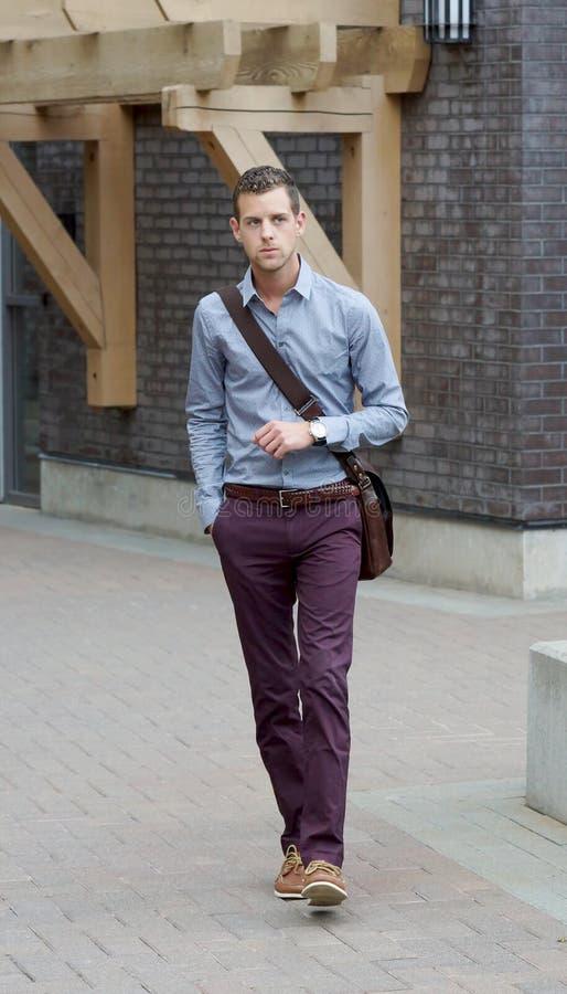 Giovane maschio adulto bello che cammina con un messaggero Bag immagine stock libera da diritti