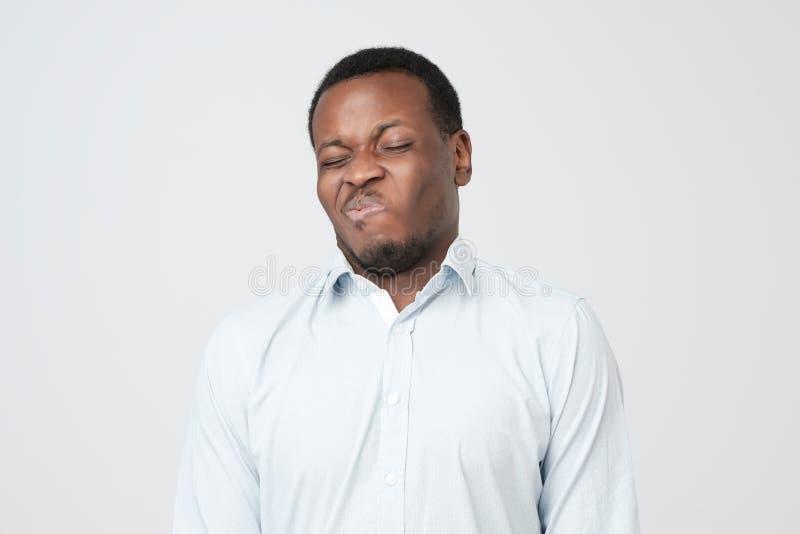 Giovane maschio afroamericano disgustato che guarda nel disprezzo, ritenendo detestare e repulsione fotografia stock libera da diritti