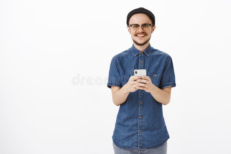 Giovane maschio bello piacevole con la barba e baffi in vetri e smartphone nero della tenuta del beanie che guardano fisso con immagine stock
