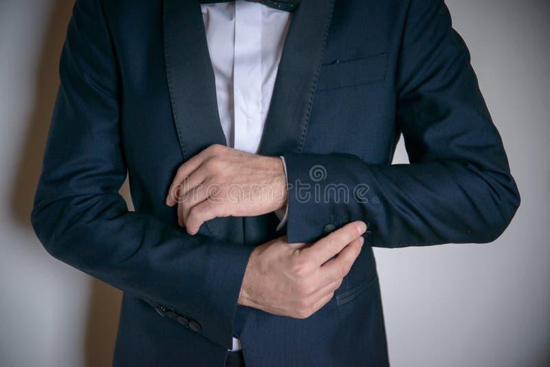 Giovane maschio caucasico bello che indossa vestito scuro di classe e che ripara elegante la manica immagine stock