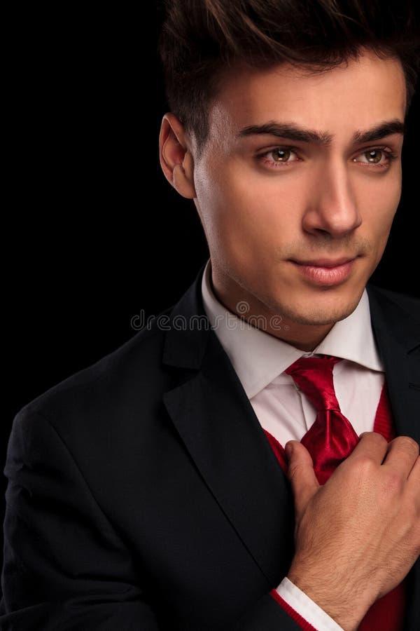 Giovane maschio di classe in vestito nero che ripara il suo legame immagini stock