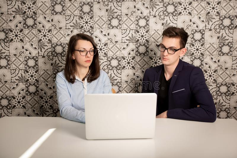 Giovane maschio e soci commerciali femminili che si siedono dietro un monitor del computer e che pensano a qualcosa immagine stock