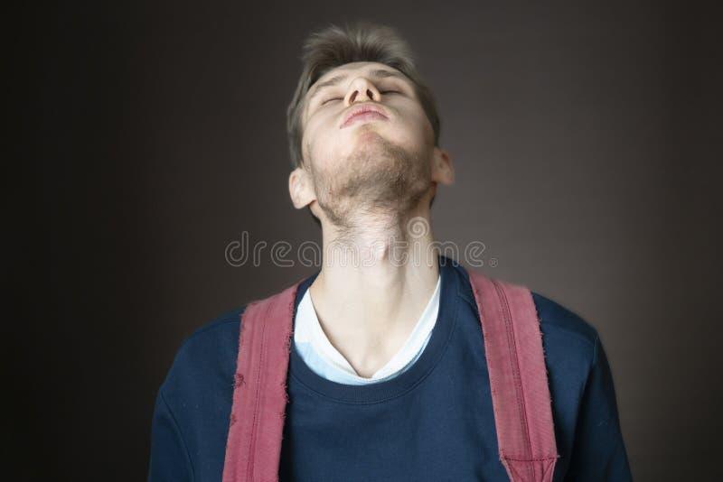 Giovane maschio sorridente bello con lo zaino in casuale su fondo scuro f fotografia stock libera da diritti