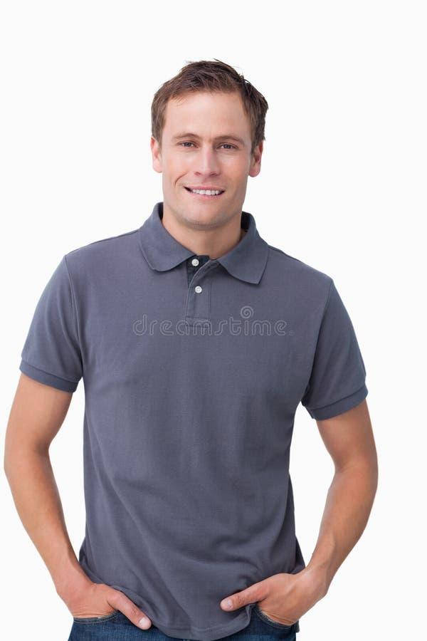 Giovane maschio sorridente con le mani in sue caselle immagine stock libera da diritti