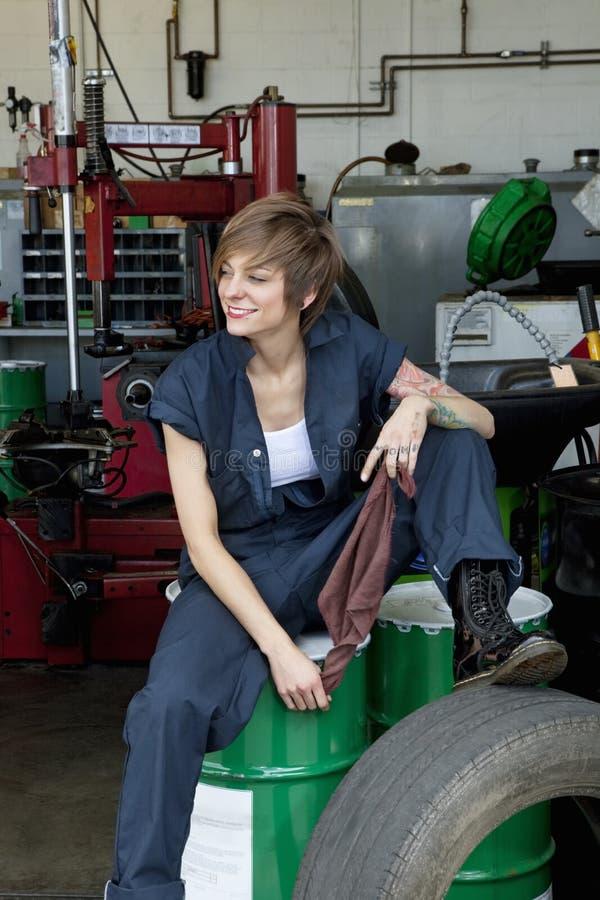 Giovane meccanico femminile felice che si siede sul tamburo dell'olio nell'officina riparazioni dell'automobile fotografia stock
