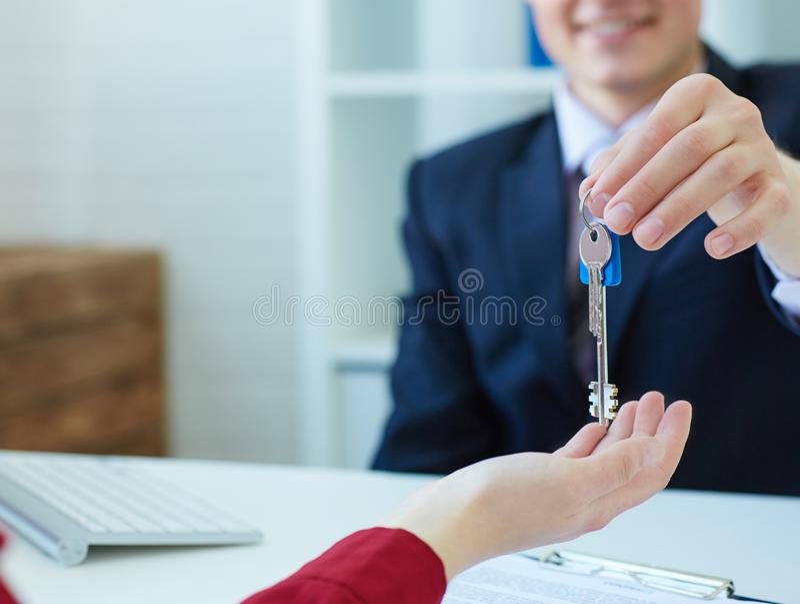 Giovane mediatore maschio che fornisce le chiavi di nuova casa al cliente femminile fotografia stock