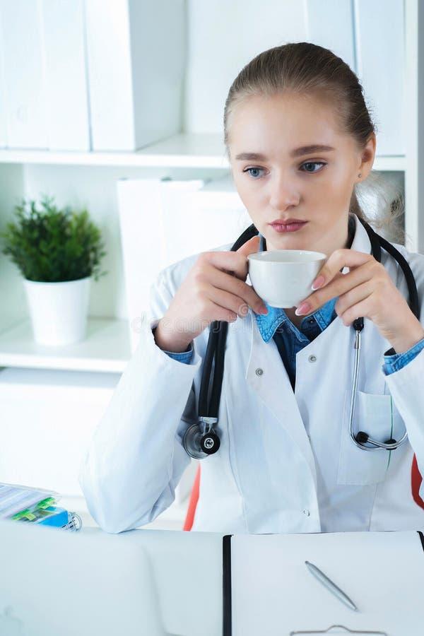 Giovane medico caucasico femminile che ha una rottura e che beve caffè che si siede nel suo luogo di lavoro immagini stock libere da diritti