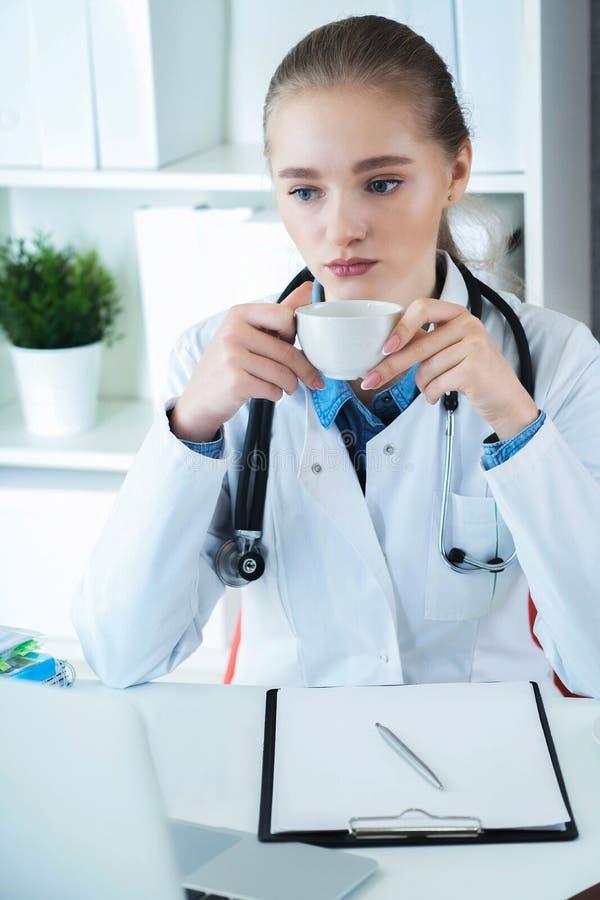 Giovane medico caucasico femminile che ha una rottura e che beve caffè che si siede nel suo luogo di lavoro fotografia stock