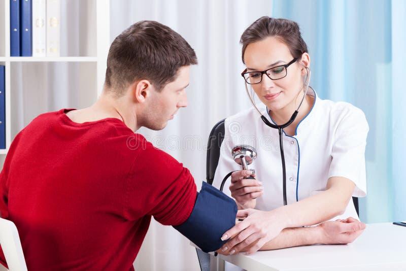 Giovane medico che esamina un paziente nel suo ufficio immagine stock