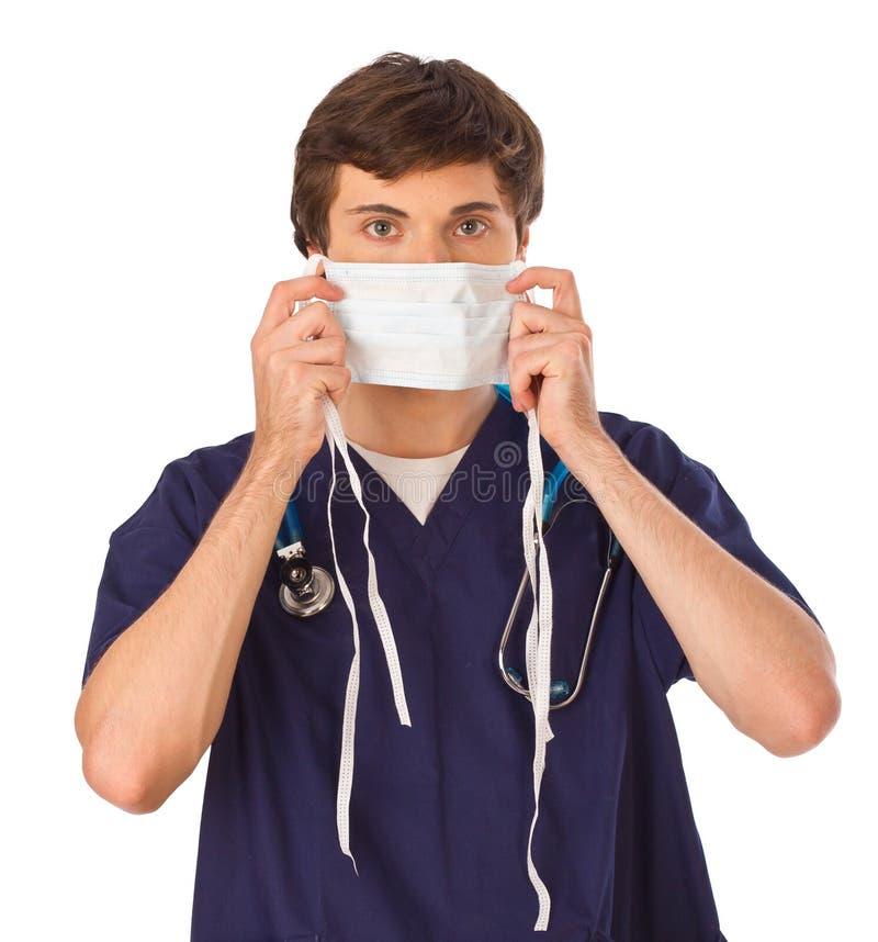 Giovane medico che mette sulla mascherina immagine stock libera da diritti