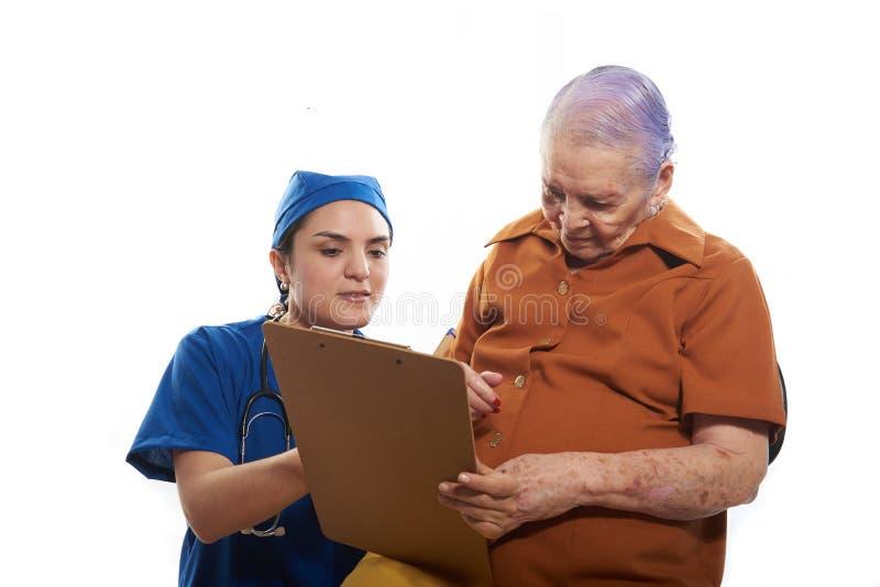Giovane medico che mostra lavagna per appunti al paziente fotografie stock libere da diritti