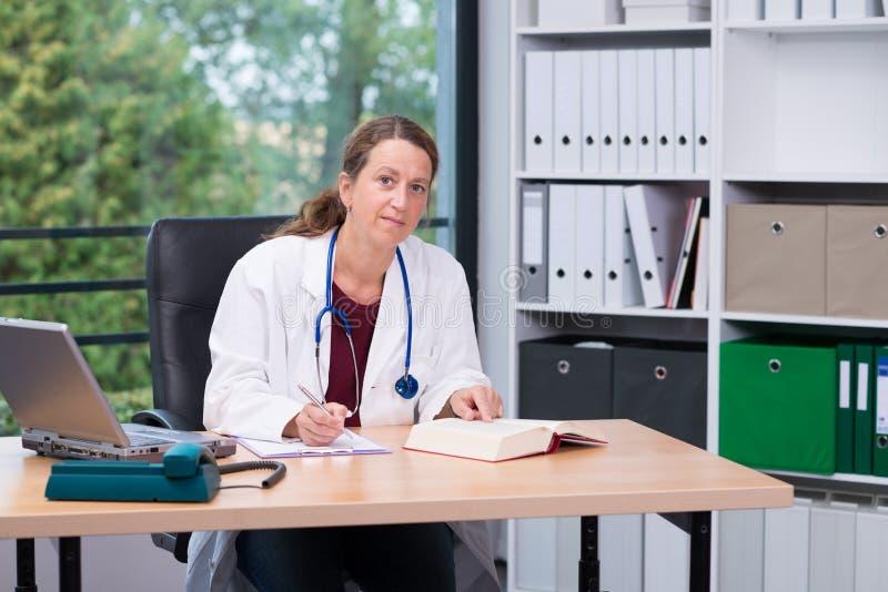 Giovane medico di famiglia femminile nel suo ufficio fotografia stock