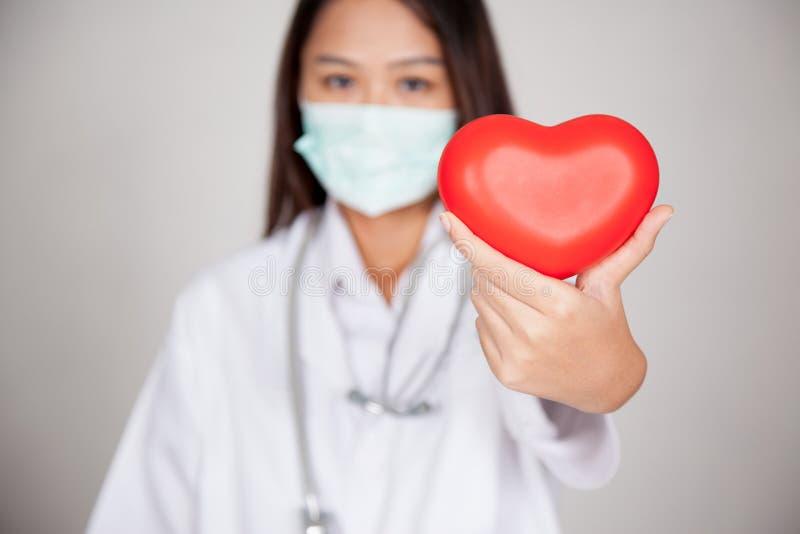 Giovane medico femminile asiatico con cuore rosso fotografie stock libere da diritti